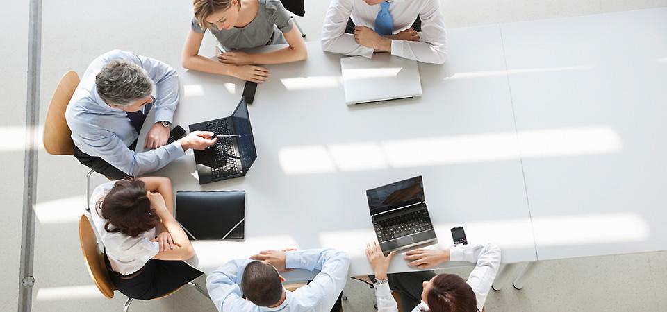 Ein Sprachkurs in Düsseldorf wird abgehalten. Sprachlehrer und Kursteilnehmer sitzen am Tisch.