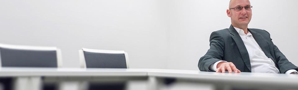 Der Geschäftsinhaber der Sprachschule Wuppertal sitzt im Kursraum am Tisch.